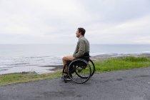 Вид збоку молодого Кавказького чоловіка в інвалідному візку, насолоджуючись день у моря, насолоджуючись видом — стокове фото