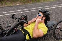 Вид збоку крупним планом молодого Кавказького чоловіка в спортивному одязі на лежачому велосипеді велоспорту на заміському шляху, кріплення шолома — стокове фото