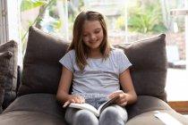 Вид спереди улыбающейся белой девочки, сидящей на удобном кресле и читающей в своей гостиной — стоковое фото
