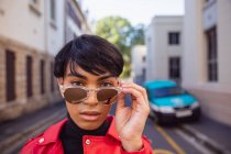 Verticale d'un jeune adulte transgenre mélangé à la mode de course dans la rue, enlevant des lunettes de soleil outre — Photo de stock