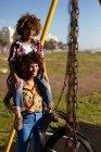 Vista frontal close-up de uma jovem mulher de raça mista e seu filho pré-adolescente desfrutando de tempo juntos jogando em um playground, a mulher carrega seu filho piggyback em um dia ensolarado com oscilações em primeiro plano — Fotografia de Stock