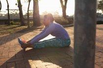 Вид сбоку на молодую кавказскую женщину в спортивной одежде, сидящую и держащую лодыжки с вытянутыми перед ней ногами во время тренировки в парке — стоковое фото