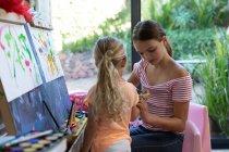 Vista frontal de uma jovem caucasiana e sua irmã tween pintura juntos em casa — Fotografia de Stock