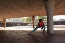 Vista frontale di una giovane donna caucasica che indossa vestiti sportivi accovacciati e si estende sotto un ponte durante un allenamento in un parco — Foto stock