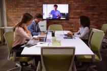 Vista laterale di una giovane donna di razza mista e di una giovane donna e uomo caucasici che lavorano nell'ufficio di un'azienda creativa . — Foto stock