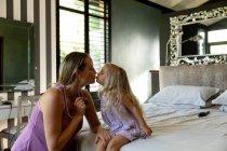 Vista lateral de una joven mujer embarazada caucásica besando a su hija en su dormitorio. - foto de stock