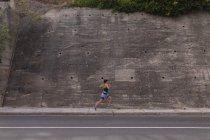 Vue latérale d'une jeune femme caucasienne portant des vêtements de sport courant devant un mur dans une rue pendant une séance d'entraînement — Photo de stock