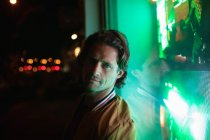 Портрет молодого кавказца, смотрящего вечером в камеру с зеленым неонным светом из окна магазина позади него — стоковое фото
