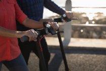 Вид збоку середині секції чоловік і жінка їзда e скутери біля моря на заході сонця — стокове фото