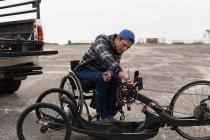Вид на молоду Кавказьку людину в інвалідному візку збірка лежачого велосипеда, фіксування ланцюга в парковій автостоянці біля моря — стокове фото