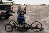 Вид на молоду Кавказьку людину в інвалідному візку збірка лежачого велосипеда, тримаючи колесо в парковій автостоянці біля моря — стокове фото