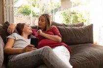 Вид спереди молодой белой беременной женщины, разговаривающей со своей дочерью-подростком, сидящей на диване в их гостиной, девушка держит смартфон — стоковое фото