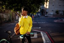 Front view of a fashionable young mixed race transgender adult in the street, standing and holding a bike — Stock Photo