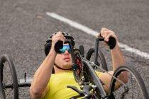 Зовнішній вигляд крупним планом молодого Кавказького чоловіка в спортивному одязі на лежачому велосипеді велоспорту на заміському шляху — стокове фото