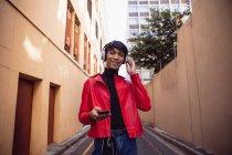 Retrato de un joven transexual de raza mixta de moda en la calle, usando un teléfono inteligente con auriculares sonriendo a la cámara - foto de stock