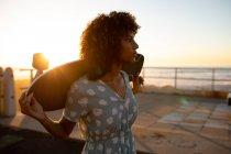 Vue latérale rapprochée d'une jeune femme métissée tenant une planche à roulettes sur ses épaules admirant la vue sur la mer, rétroéclairée par le soleil couchant — Photo de stock