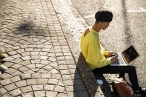 Side view of a fashionable young mixed race transgender adult in the street, using a laptop computer sitting on steps — Stock Photo