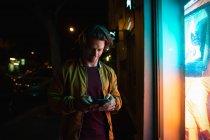 Вид спереди улыбающегося молодого кавказца, стоящего ночью у витрины магазина с помощью смартфона — стоковое фото