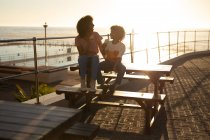 Front view of a mixed race woman and her pre-teen son enjoying time together by the sea, smiling and eating ice cream siting on a picnic table on a sunny day — Stock Photo