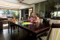 Vorderansicht einer jungen kaukasischen Frau, die mit ihren Zwillingen und jüngeren Töchtern im Wohnzimmer bastelt — Stockfoto