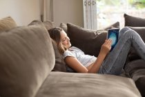 Side view of a tween Caucasian girl reading in sitting room — Stock Photo