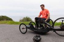 Вид на молодий Кавказький чоловік у спортивному одязі на вихід з інвалідному візку в лежачий велосипед на заміському шляху — стокове фото