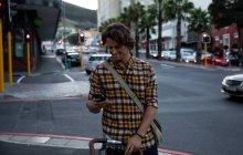 Вид спереди на молодого кавказца, стоящего на городской улице, держащего велосипед и пользующегося смартфоном вечером — стоковое фото