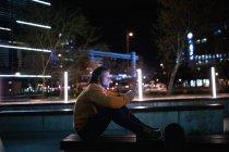 Vista lateral de un joven caucásico sentado en una pared en la calle por la noche hablando por teléfono con auriculares encendidos, con un monopatín a su lado - foto de stock