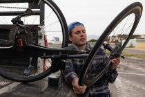 Вид спереду крупним планом молодого Кавказького чоловіка в інвалідному візку приймаючи лежачий велосипед з задньої частини своєї машини, щоб зібрати його на автостоянці біля моря — стокове фото
