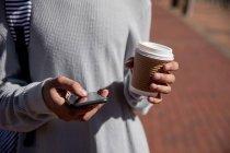 Vista frontal seção média de um homem na moda na rua, mensagens de texto no smartphone e segurando uma xícara de café — Fotografia de Stock
