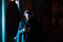 Вид спереди на молодого кавказца, стоящего ночью на улице и слушающего музыку в наушниках, смотрящего на смартфон — стоковое фото