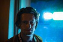 Ritratto di un giovane caucasico che guarda alla telecamera la sera con una luce blu al neon da una vetrina dietro di lui — Foto stock