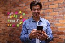 Вид спереди на улыбающегося молодого кавказца с помощью смартфона, стоящего в офисе креативного бизнеса, цветные липкие ноты на кирпичной стене на заднем плане — стоковое фото