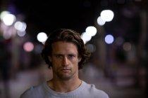 Portrait d'un jeune homme caucasien dans la rue regardant droit devant la caméra le soir — Photo de stock