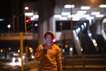Front view of a young Caucasian man in the street at night holding a smartphone and wearing earphones on, looking to camera — Stock Photo