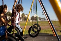 Vista lateral de uma jovem mulher de raça mista e seu filho pré-adolescente desfrutando de tempo juntos jogando em um playground, balançando em um dia ensolarado — Fotografia de Stock