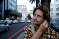 Fim da vista dianteira acima de um homem caucasiano novo que põr auriculares sobre em uma rua urbana ocupada durante sua noite comutar — Fotografia de Stock