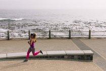 Vista laterale di una giovane donna caucasica che indossa abiti sportivi in esecuzione durante un allenamento in una giornata di sole sul mare — Foto stock