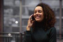 Вид спереди крупным планом улыбающейся молодой женщины смешанной расы, стоящей и разговаривающей по смартфону в офисе креативного бизнеса — стоковое фото