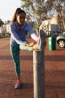 Front view close up of a young Caucasian woman wearing sports clothes leaning on a post stretching her leg while working out in a park — Stock Photo