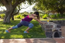 Side view of a young Caucasian woman wearing sports clothes pushing against a wall and stretching during a workout in a park — Stock Photo