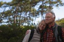 Vista frontal close-up de um homem e mulher caucasiano maduro abraçando com os olhos fechados durante uma caminhada em um ambiente rural — Fotografia de Stock