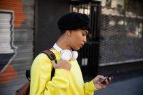 Vista lateral de un joven adulto transgénero de raza mixta de moda en la calle, utilizando un teléfono inteligente, en una boina y auriculares - foto de stock