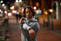 Portrait d'un jeune homme caucasien s'étirant dans la rue pendant son entraînement en fin de soirée — Photo de stock