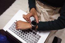 Vista frontal sección media de la mujer comprobando su reloj inteligente y el uso de una computadora portátil en la oficina de un negocio creativo - foto de stock
