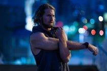 Vista frontale di un giovane atletico caucasico che si allena in un parco cittadino la sera, allungando le braccia con luci della città sfocate sullo sfondo — Foto stock