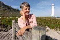 Vista frontale di una donna caucasica di mezza età che si gode il tempo libero seduti su una panchina rilassandosi su una spiaggia soleggiata vicino a una casa luminosa vicino al mare in una giornata invernale soleggiata — Foto stock