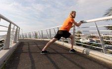 Vue latérale d'un jeune homme athlétique caucasien faisant de l'exercice sur une passerelle dans une ville, s'étirant et s'appuyant sur la main courante — Photo de stock