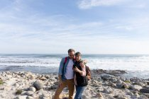 Frontansicht eines kaukasischen Paares, das ein Smartphone benutzt, während es an einem sonnigen Tag die freie Zeit am Meer am Strand genießt — Stockfoto