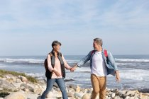 Front view of an adult Caucasian couple enjoying free time walking on a beach and smiling beside the sea on a sunny day — Stock Photo